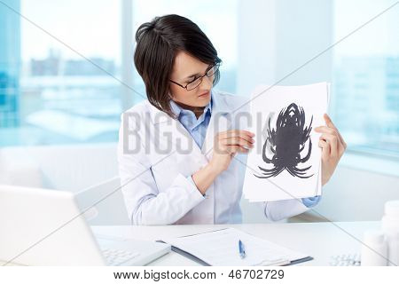 Young psychologist looking at paper with Rorschach inkblot