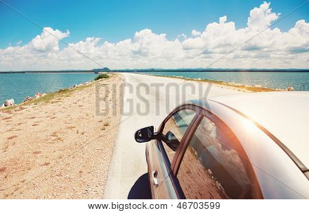 Car driving across ocean by the road