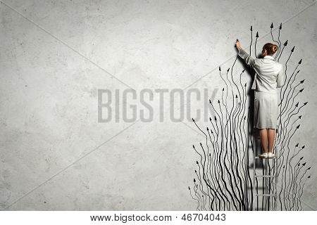 Woman standing on ladder drawing on wall