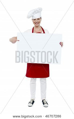 Experienced Cook Indicating At White Banner