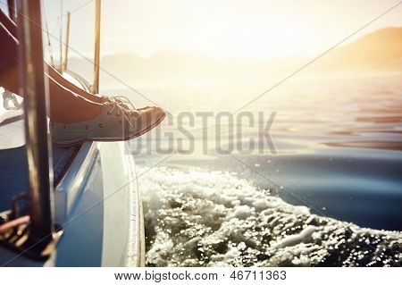 feet on boat sailing at sunrise lifestyle