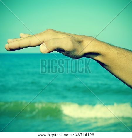 picture of a man waving free his hand in the air with the ocean at the background, with a retro effect