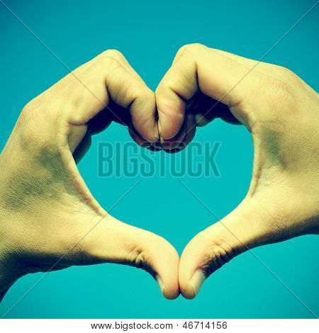 picture of man hands forming a heart over the blue sky, with a retro effect