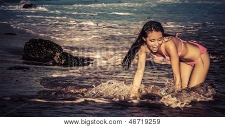 Beautiful happy carefree woman in bikini on beach splashing in ocean water