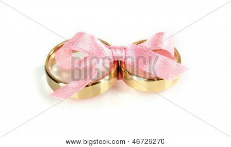 Wedding rings tied with ribbon isolated on white