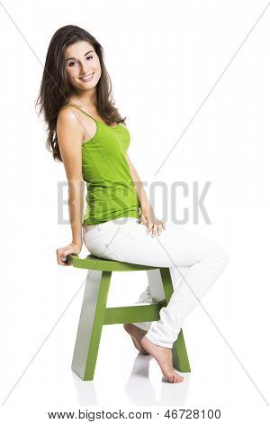 Beautiful young woman sitting in a green chair, isolated over a white background