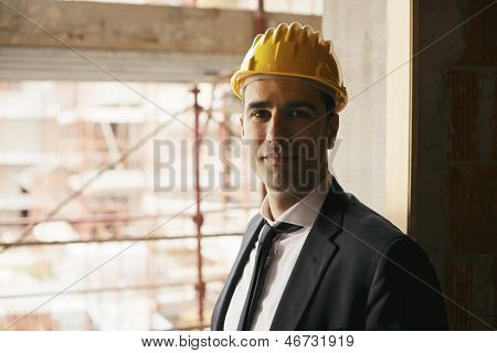 Engineer With Helmet In Construction Site Smiling At Camera, Portrait