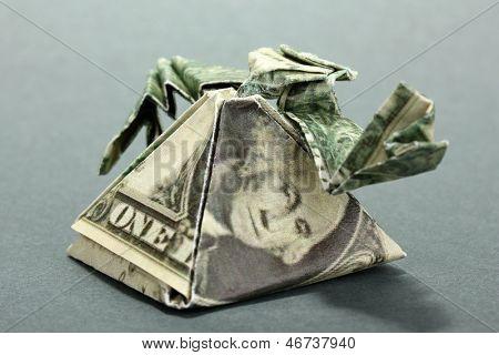Dollar folded into Egyptian pyramid on grey background
