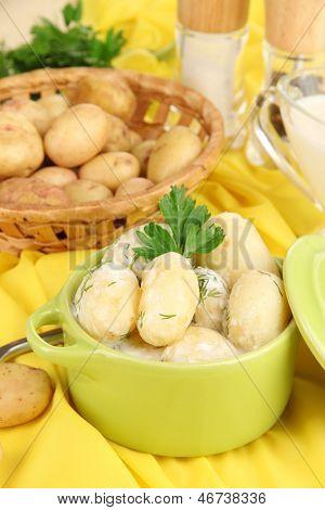 Concursos jovens batatas com creme de leite e ervas na panela em close-up de mesa de madeira