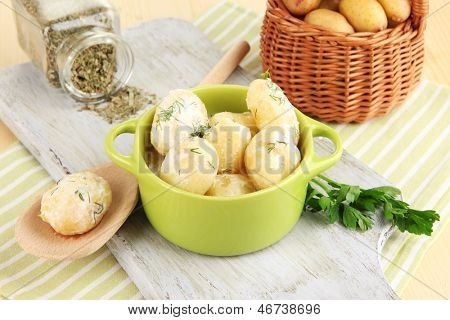 Concursos jovens batatas com creme de leite e ervas na panela na placa de madeira em close-up de tabela