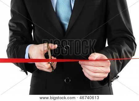 Businessman cutting red ribbon with pair of scissors close up