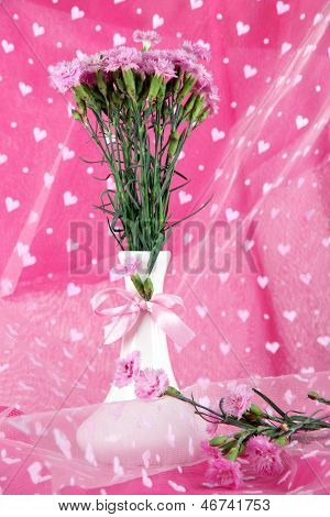 Many small pink cloves IN vase on light pink fabric background
