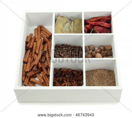 Assortment of aroma spices in white wooden box isolated on white