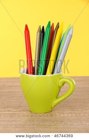 Colorful pencils in cup on table on yellow background