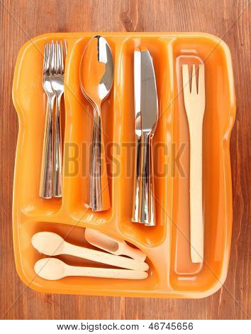 Orange plastic cutlery tray with checked cutlery and wooden spoons on wooden table