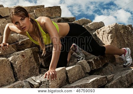 Beautiful young caucasian woman in fitwear climbing on the old brick wall