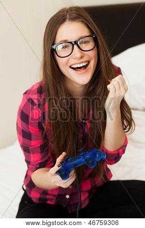 Young beautiful woman in casual playing videogame at home