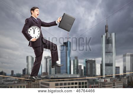 Full length portrait of a businessman holding clock and briefcase, walking on a rope, with the financial centre in Frankfurt, Germany in the background