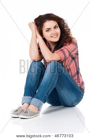 Beautiful girl sitting on floor and looking at camera