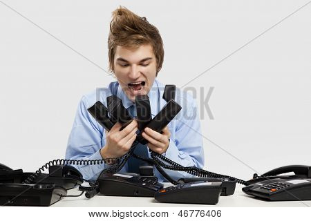 Young man holding and yelling to the phones