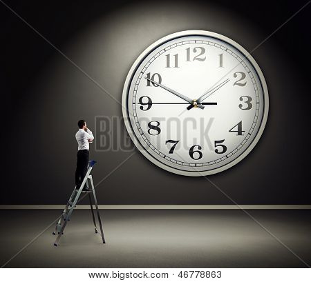 thoughtful businessman standing on the pair of steps and looking at big clock