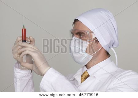 Confident surgeon holding a syringe against a white background