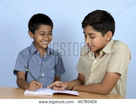 Handsome Indian toddler being coached by his brother