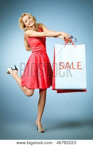 Portrait of a beautiful young woman carrying shopping bags.