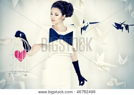 Art fashion photo of a gorgeous woman in paper dress holding birdcage with red heart. Black and white.