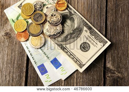 US and euro currency over wooden background