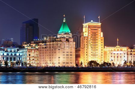 Shanghai historic architecture at night lit by lights over Huangpu River