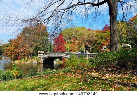 New York City Manhattan Central Park panorama in Autumn lake with bridge skyscrapers and colorful trees with reflection.