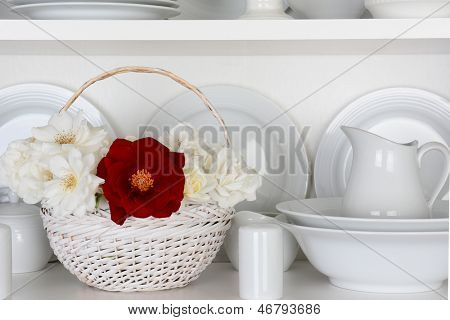 Closeup of a  basket of roses on the shelf of a cupboard full of white plates. Items include, plates, saucers, bowls and a gravy boat. There is one red rose amongst all the white.