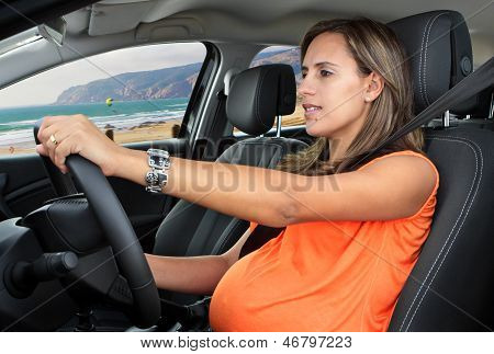 Pregnant Woman Driving A Car On Coastal Road