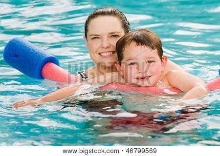 Mother giving son a swimming lesson in pool during summer