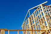 stock photo of framing a building  - New residential construction house framing against a blue sky - JPG