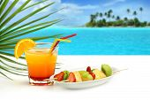 stock photo of fruits  - summer cocktail and fruit skewers on exotic seascape - JPG