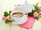 stock photo of dog-rose  - Cup and teapot of herbal tea with hip rose flowers on white wooden table - JPG