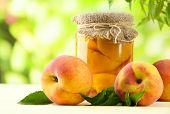 stock photo of peach  - Jar of canned peaches and fresh peaches on wooden table - JPG