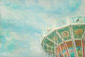 stock photo of carnival ride  - Closeup of a colorful carousel with blue sky background with painterly textured editing - JPG