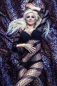 Постер, плакат: Сексуальная блондинка девушка на кровати фон гепард