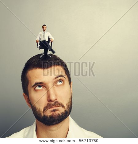 surprised man looking up at small successful man on the head