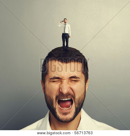 small man with gun holding on the head of stressed man