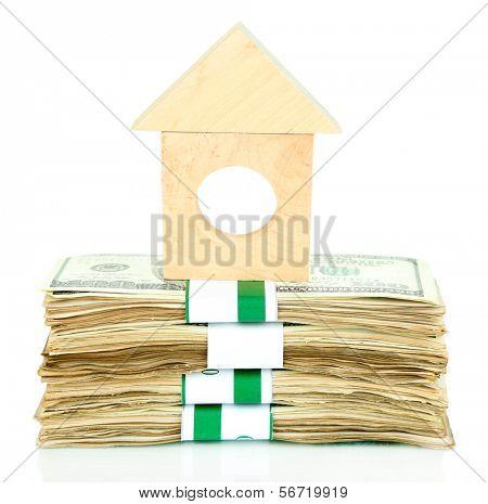 Casa de madera en los paquetes de dólares aislados en blanco
