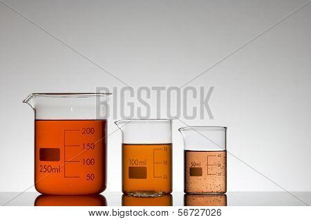 tres vasos de laboratorio líquido naranja