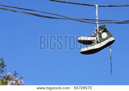 sneakers hanging from electrical wire against a blue sky
