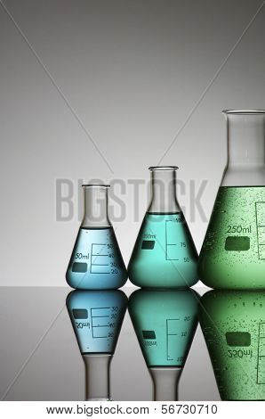 group of three conical flasks containing liquid
