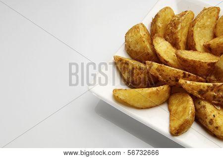 voorhoede van een gebakken aardappel segmenten op een witte plaat