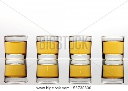 Four small shot glasses of whiskey