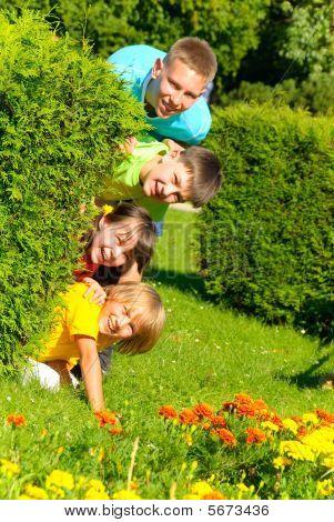 Cousins behind bush